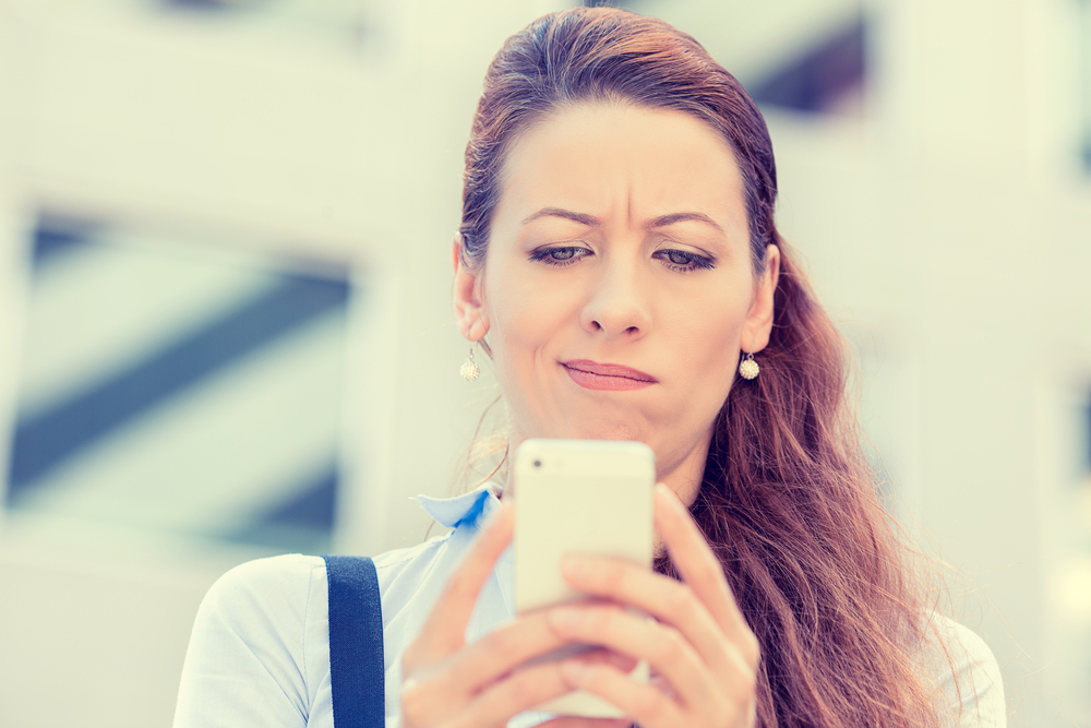Closeup side profile portrait upset sad skeptical unhappy serious woman talking texting on phone displeased with conversation isolated city background. Negative human emotion face expression feeling-1
